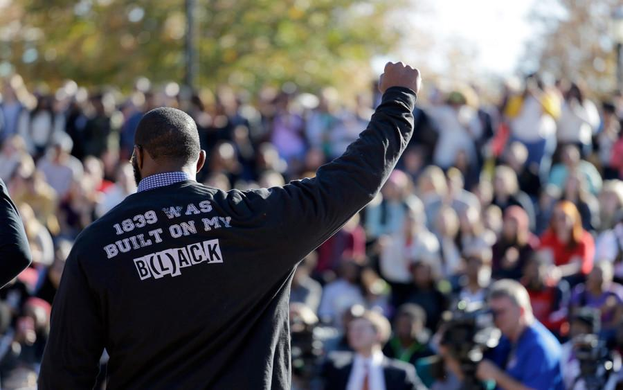 A member of the black student protest group Concerned Student 1950 gestures while addressing a crowd following the announcement that University of Missouri System President Tim Wolfe would resign Monday, Nov. 9, 2015, at the university in Columbia, Mo. Wolfe resigned Monday with the football team and others on campus in open revolt over his handling of racial tensions at the school. (AP Photo/Jeff Roberson)