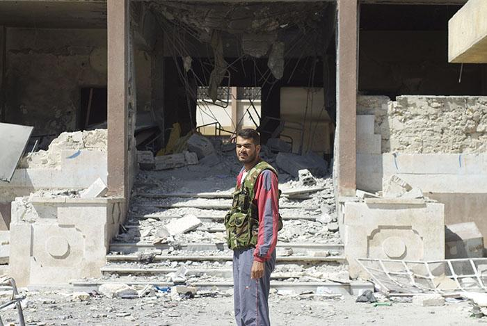 A Syrian rebel stands in front of a school on September 13, 2012, hit by a Syrian government air strike in Aleppo, Syria. (David Enders/MCT)