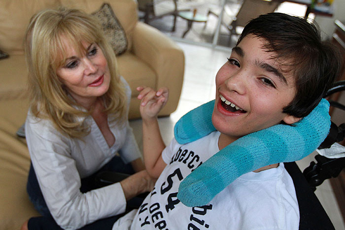 Judy Susser, left, of Boca Raton, Florida, is pictured December 6, 2012, with her disabled son Adam, 12, who has received stem-cell treatments. Adam was born with brain damage, was blind and has cerebral palsy. He now is able to see enough to track movement, including icons on his iPad. (Carline Jean/Sun Sentinel/MCT)
