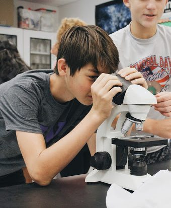 "Investigating a mock murder case, freshman Jared Fitch examines samples through a microscope. ""I expected to be learning about the human body and other biological lessons, but I didn't didn't expect we'd be learning about other jobs that biomedical sciences could lead to,"" Fitch said."