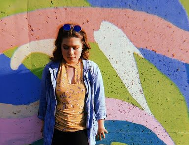 Sophomore Addison Jett poses in front of a funky mural in Chesterfield Valley.