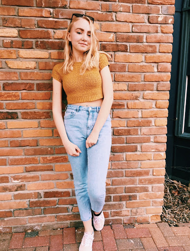 Junior Makena Schroeder poses on a brick wall in Main Street St. Charles.
