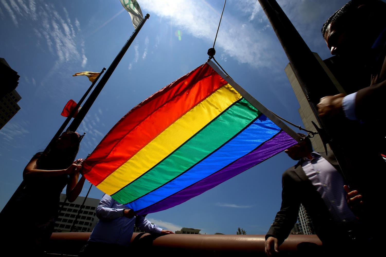 A pride flag is being held in honor of pride month.