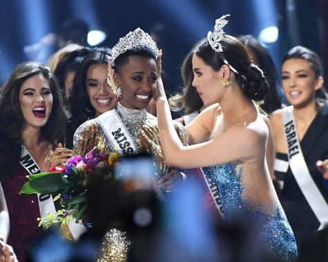 Miss Universe 2019 Zozibini Tunzi, of South Africa, is crowned onstage by Miss Universe 2018 Catriona Gray (right, in blue) at the 2019 Miss Universe Pageant at Tyler Perry Studios on Sunday, Dec. 8, 2019 in Atlanta, Ga. (Paras Griffin/Getty Images/TNS)