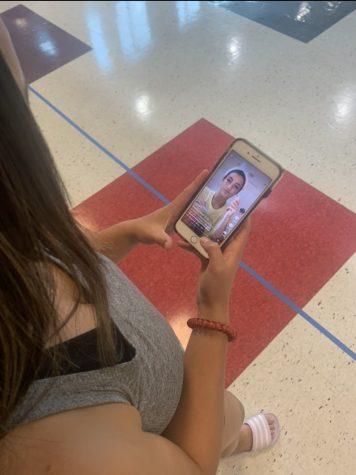 Student watching TikTok on their cellular device.