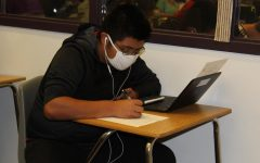 Student quietly studies while listening to music to help with the background noise.