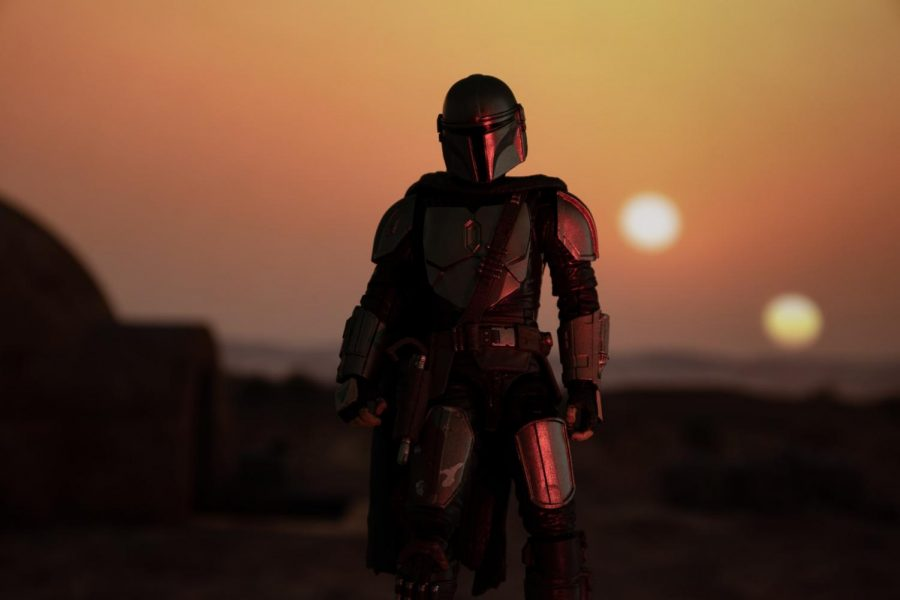The Mando stands in front of Tatooine's setting twin suns.