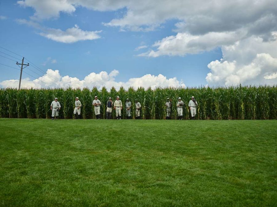 Field of Dreams actors walk out of the cornfield.